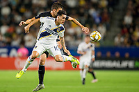 CARSON, CA - SEPTEMBER 15: Daniel Steres #5 of the Los Angeles Galaxy and Graham Smith #16 of Sporting Kansas City battle for a loose ball during a game between Sporting Kansas City and Los Angeles Galaxy at Dignity Health Sports Park on September 15, 2019 in Carson, California.