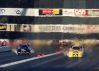 Nov 9, 2013; Pomona, CA, USA; NHRA funny car driver Bob Bode (right) races alongside Josh Crawford during qualifying for the Auto Club Finals at Auto Club Raceway at Pomona. Mandatory Credit: Mark J. Rebilas-