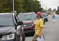 Katherine Birkhead of the NAACP reminds drivers waiting at a mobile food pantry to complete their census, Friday, September 11, 2020 at the Springdale Senior Center in Springdale. The senior center hosted a food drive by the Northwest Arkansas Food Bank. They handed out enough food for 310 families. The food bank distributes at the site every second Friday of the month, but they will move their mobile pantry to Parson's Arena starting October. In addition, members of the League of Women Voters also helped register people to vote and reminded them to complete the census. Check out nwaonline.com/200912Daily/ for today's photo gallery. <br /> (NWA Democrat-Gazette/Charlie Kaijo)