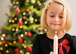 Girl (6-7) with candlestick in front of Christmas tree