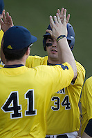 Michigan Wolverines designated hitter Kyle Jusick (34) is greeted by teammate Dominic Jamett (41) after scoring during the NCAA season opening baseball game against the Texas State Bobcats on February 14, 2014 at Bobcat Ballpark in San Marcos, Texas. Texas State defeated Michigan 8-7 in 10 innings. (Andrew Woolley/Four Seam Images)