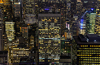 USA, New York City, Manhattan skyscraper with illuminated offices and apartments at night viewed from Rockefeller Center, top of the rock