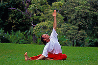 Man practicing yoga on a green lawn in Hawaii.