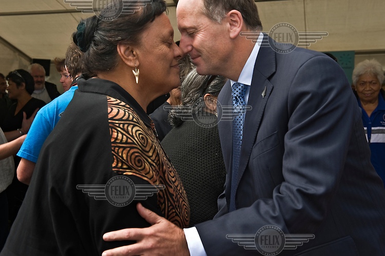 The Prime Minister of New Zealand, John Key, greets a woman in the Maori manner with with a hongi (touching noses and foreheads), during the opening of Te Uku Wind farm near Raglan on the West Coast of the North Island.