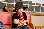 Education Preschool 3-5 year olds dressup pretend play boy in hat and jacket holding doll horizontal