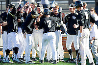Joey Rodriguez (7) of the Wake Forest Demon Deacons is greeted by teammates after scoring a run in the bottom of the 9th inning against the Youngstown State Penguins at Wake Forest Baseball Park on February 24, 2013 in Winston-Salem, North Carolina.  The Demon Deacons defeated the Penguins 6-5.  (Brian Westerholt/Four Seam Images)
