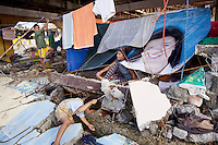 Philippines. Province Eastern Samar. Hernani. Jaworski High School destroyed by typhoon Haiyan's winds and storm surge. A family whose house was destroyed by Typhoon Haiyan lives in a made-up ground sheet tent. The smiling face of Mikee Gojungco, Mother Advocate, Child Rights Ambassador for the Non-governmental organization (NGO) Plan Phiippines. Laudry drying on a rope. Typhoon Haiyan, known as Typhoon Yolanda in the Philippines, was an exceptionally powerful tropical cyclone that devastated the Philippines. Haiyan is also the strongest storm recorded at landfall in terms of wind speed. Typhoon Haiyan's casualties and destructions occured during a powerful storm surge, an offshore rise of water associated with a low pressure weather system. Storm surges are caused primarily by high winds pushing on the ocean's surface. The wind causes the water to pile up higher than the ordinary sea level. 24.11.13 © 2013 Didier Ruef
