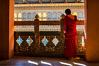 A lone buddhist monk looks down from the ornate gallery to the interior courtyards of Punakha Dzong