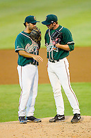 Greensboro Grasshoppers shortstop Anthony Gomez (2) has a chat on the mound with relief pitcher Matt Milroy (40) during the South Atlantic League game against the Kannapolis Intimidators at CMC-Northeast Stadium on July 12, 2013 in Kannapolis, North Carolina.  The Grasshoppers defeated the Intimidators 2-1.   (Brian Westerholt/Four Seam Images)
