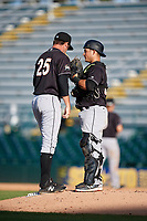 Jupiter Hammerheads relief pitcher Chad Smith (25) talks with catcher Chris Hoo (18) during the second game of a doubleheader against the Bradenton Marauders on May 27, 2018 at LECOM Park in Bradenton, Florida.  Jupiter defeated Bradenton 4-1.  (Mike Janes/Four Seam Images)