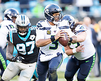 CHARLOTTE, NC - DECEMBER 15: Russell Wilson #3 of the Seattle Seahawks evades the pass rush during a game between Seattle Seahawks and Carolina Panthers at Bank of America Stadium on December 15, 2019 in Charlotte, North Carolina.