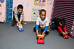 Education Preschool 4 year olds group of three boys racing vehicles in classroom