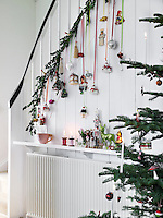 A festive array of decorations hang from spruce branches on the staircase