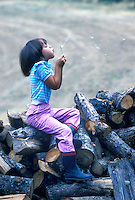 Small girl on woodpile blowing bubbles. Monroe, Oregon.