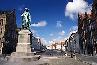 Brugge, Belgium, Bruges, West-Vlaanderen, Europe. Monument along a cobbled canal street in downtown Bruges.