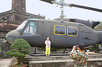 Vietnam. Hanoi. Military history museum. A vietnamese father is taking pictures of his daughter standing near a Bell UH-1H Iroquois helicopter gunship. A military aircraft taken by north vietnamese troops during the war against USA. Foreign tourits are visiting the museum. 04.04.09 © 2009 Didier Ruef