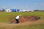 Mark Belsham of England plays his ball out of the bunker alongside the 13th green during day one of The Senior Open Golf Tournament at The Royal Porthcawl Golf Club in South Wales this afternoon.