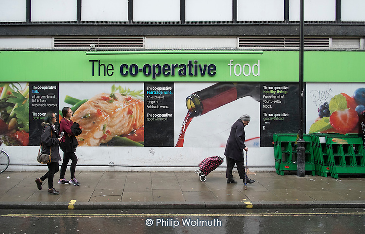 Elderly woman with a shopping trolley at a co-operative supermarket, Soho, London.