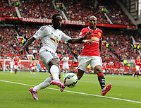 Pictured L-R: Nathan Dyer of Swansea crossing the ball, marked by Ashley Young of Manchester United.  Saturday 16 August 2014<br />