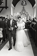 Black and white shot of bride and groom coming down the aisle after the ceremony.