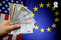 Man's hand with US and Euro banknotes on European Union and US Flag (Licence this image exclusively with Getty: http://www.gettyimages.com/detail/sb10068346ao-001 )
