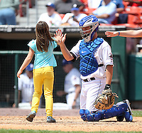 Buffalo Bisons catcher Josh Thole, on rehab assignment from the NY Mets, gives a high five to a young fan participating in the base race during a game against the Columbus Clippers at Coca-Cola Field on May 31, 2012 in Buffalo, New York.  Columbus defeated Buffalo 3-0.  (Mike Janes/Four Seam Images)