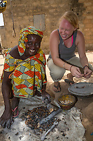 Peace Corps Volunteer Working with Village Woman Removing Hulls from Cashew Nuts, Nixo Village, near Sokone, Senegal