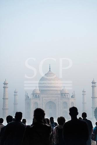 Agra, Uttar Pradesh, India. Taj Mahal in the mist at dawn, tourists in silhouette.