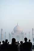 Agra, Uttar Pradesh, India. Taj Mahal in the mist at dawn, tourists in silhouette.