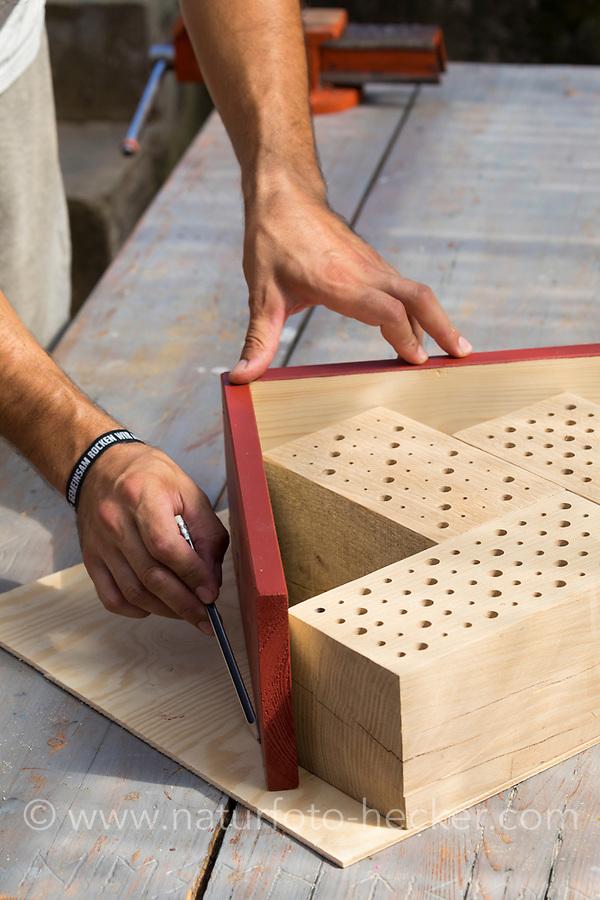 """Wildbienen-Nisthilfe Modell """"Blockhütte"""". Die aneinander geleimten Holzblöcke und das montierte Dach werden auf eine Sperrholzplatte gelegt, Rückwand und die Konturen angezeichnet. Besteht aus Hartholzblöcken mit unterschiedlichen Bohrungen, Schilfstängeln, Natur-Strohhalmen und Pappröhrchen, Wildbienen-Nisthilfen, Wildbienen-Nisthilfe selbermachen, selber machen, Wildbienenhotel, Insektenhotel, Wildbienen-Hotel, Insekten-Hotel"""