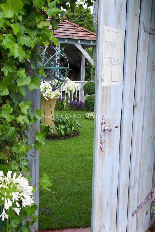 Secret garden door into lawn, gazebo, armillary sundial, climbing Hedera ivy vine, white agapanthus summer flowering bulbs, lawn grass, open blue door with sign saying Private Garden . Board and batten door