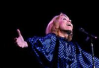 """Isabelle Aubray in concert, circa 1986<br /> <br /> Thérèse Coquerelle dite Isabelle Aubret<br /> <br /> Née le 27 juillet 1938 ? Lille<br /> <br /> Bobineuse mais également gymnaste de talent (elle décroche le titre de championne de France en 1952), Thérèse Coquerelle, qui ne tardera pas ? se faire appeler Isabelle Aubret, montre par ailleurs des prédispositions pour la chanson.<br /> Au début des années 60, elle se produit dans des orchestres avant de se retrouver sur la scène de l'Olympia ? la faveur d'un concours. Bruno Coquatrix, le maître des lieux, qui la remarque, lui permet d'effectuer ses véritables débuts dans un cabaret parisien, le Fifty-Fifty.<br /> Autre rencontre déterminante pour Isabelle Aubret, celle qu'elle fait avec Jacques Canetti, découvreur de talents, notamment Charles Aznavour ou encore Edith Piaf. L'agent artistique lui fait enregistrer son premier 45 tours, signé Maurice Vidalin. Et en 1962 c'est la consécration au concours de l'Eurovision avec """" Un premier amour """".<br /> <br /> La rencontre avec Ferrat<br /> <br /> C'est cette m?me année qu'elle se lie d'une amitié, qui s'avèrera sans faille, avec Jean Ferrat, qui lui écrit """" Deux enfants au soleil """". Il lui propose également la première de sa tournée.<br /> Décidemment très sollicitée, Isabelle Aubret est en première partie de Jacques Brel ? l'Olympia. Toujours en 1963, elle est aux côtés de Sacha Distel.<br /> Elle est également appelée par Jacques Demy et Michel Legrand qui travaillent sur """" Les parapluies de Cherbourg """" et entendent lui confier le rôle principal. Le projet ne se concrétisera jamais, du moins pour Isabelle Aubret qui est victime d'un dramatique accident de la route qui lui voudra une quinzaine d'interventions chirurgicales et des années de rééducation.<br /> En 1964, la chanteuse, qui ne manque pas de volonté, revient ? la chanson ? la faveur de """" C'est beau la vie """", écrite par Jean Ferrat. Un titre qui lui vaut un large succès un an plus tard.<br /> Toujours en rééd"""