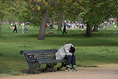 Man sleeping on a park bench, Kensington Gardens, London.