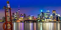Beautiful view of Toronto city skyline from harbor piers, with lit-up buildings and life buoy foreground under a purple twilight sky, Ontario Canada
