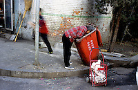 CHINA. Beijing. The wealth gap in China is huge as a woman scavenges for food in a bin in an old hutong (traditional home) in the central Niu Jie district, earmarked to be destroyed to make may for new developments aimed at modernising the city for the 2008 Summer Olympics. 2005