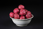 Red potatoes in white antique bowl on black background.