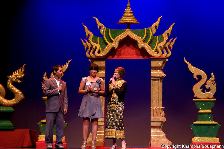 Mali Kouanchao, center, is presented with an acheivement award by Aloun Khotisene and Ketsana Vilaylack during the first annual Lao Artists Festival in Elgin, IL on August 21, 2010.  (photo by Khampha Bouaphanh)