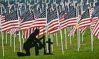 A silhouette of a soldier kneeling at a gravesite sits at the edge of a field of 3,000 flags installed in a wheat field in Maria Stein, Ohio, Monday, September 11, 2006. The display was erected to honor military, police, fire fighters, and emergency workers on the anniversary of the attacks on the World Trade Center and Pentagon in 2001.<br />