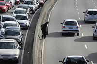 SAO PAULO, SP, 28-04-2014, IMPRUDENCIA. Flagrante de imprudencia na Av. Tiradentes no bairro da Luz,  manhã dessa segunda-feira (28), um morador de rua atravessa tranquilamente a via onde os veiculos passam em velocidade.        Luiz Guarnieri/ Brazil Photo Press.