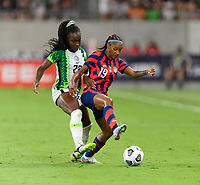 AUSTIN, TX - JUNE 16: Crystal Dunn #19 of the United States battles Michelle Alozie #22 of Nigeria for the ball during a game between Nigeria and USWNT at Q2 Stadium on June 16, 2021 in Austin, Texas.