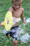 boy (4 years old) running with bubble maker and bubbles