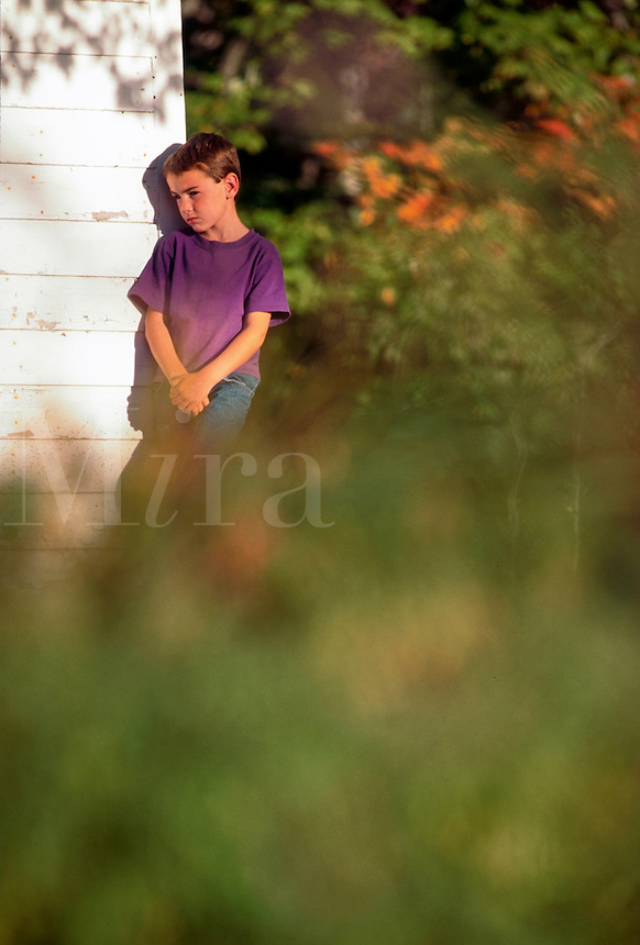 Boy looking sad and lonely standing outside his house alone.