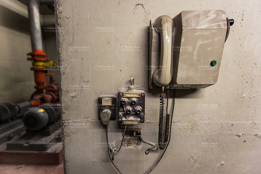 Switzerland. Canton Lucerne. Old disused and derelict telephone in the bunker of Sonnenberg tunnel in Lucerne. The Sonnenberg Tunnel is a 1,550m  long motorway tunnel, constructed between 1971 and 1976. At its completion it was also the world's largest civilian nuclear fallout shelter, designed to protect 20,000 civilians in the eventuality of war or disaster. Based on a federal law from 1963, Switzerland aims to provide nuclear fallout shelters for the entire population of the country. The construction of a new tunnel near an urban centre was seen as an opportunity to provide shelter space for a large number of people at the same time. The giant bunker was built between 1970 and 1976 at a cost of 40 million Swiss francs. The shelter consisted of the two motorway tunnels (one per direction of travel), each capable of holding 10,000 people in 64 person subdivisions. A seven story cavern between the tunnels contained shelter infrastructure including a command post, an emergency hospital, a radio studio, a telephone centre, prison cells and ventilation machines. The shelter was designed to withstand the blast from a 1 megaton nuclear explosion 1 kilometer away. The blast doors at the tunnel portals are 1.5 meters thick and weigh 350 tons. The logistical problems of maintaining a population of 20,000 in close confines were not thoroughly explored, and testing the installation was difficult because it required closing the motorway and rerouting the usual traffic. The only large-scale test, a five-day exercise in 1987 to practice converting the road tunnels into usable shelters, revealed many problems: among other things, it took 24 hours to fully close one blast door, and it proved impossible to set up the 20,000 beds within reasonable time. Afterwards, the shelter's capacity was reassessed at 10,000-17,000. Doubts about the tunnel's viability as a shelter remained. 6.02.2019 © 2019 Didier Ruef