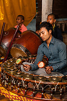 Cambodia, Angkor Wat.  Young Man Playing Cambodian Gongs.