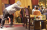 Phil Laak steps away from the table while playing a hand to stretch on a chair.
