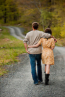 Young couple walking on country road arm in arm
