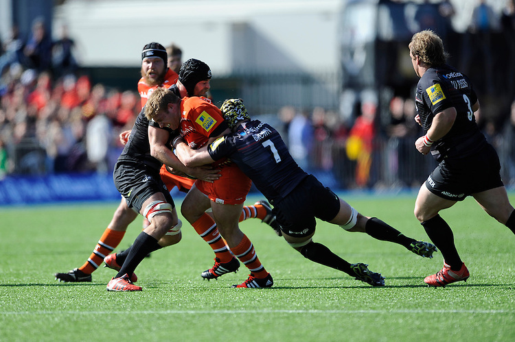 Tom Youngs of Leicester Tigers is tackled by Alistair Hargreaves and Kelly Brown of Saracens during the Aviva Premiership Rugby match between Saracens and Leicester Tigers at Allianz Park on Saturday 11th April 2015 (Photo by Rob Munro)