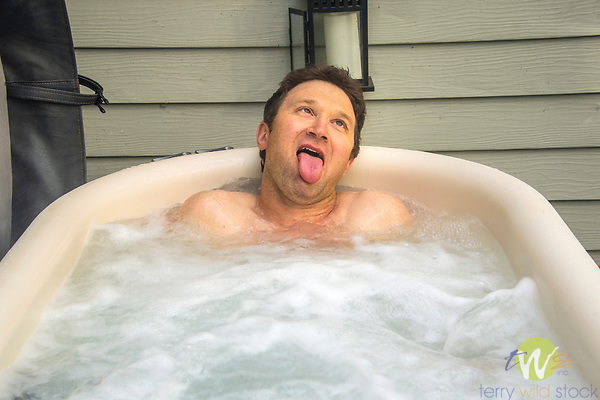 Man in hot tub making funny face.