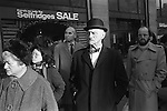 Man in bowler hat and bow tie waiting in a bus queue Oxford street. The first day of the New Years sales. London England 1976.