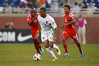 Guadeloupe midfielder David Fleurival (6) dribbles the ball past Panama defender Adolfo Machado (13) and midfielder Amilcar Henríquez (21) during the CONCACAF soccer match between Panama and Guadeloupe at Ford Field Detroit, Michigan.